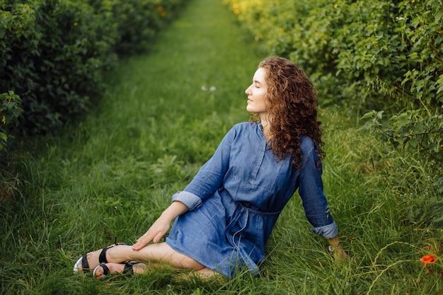 Feliz mulher jovem com cabelos cacheados castanhos, vestido, posando ao ar livre em um jardim