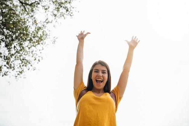 Feliz, mulher jovem, com, dela, mãos cima, vista baixa ângulo