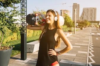 Feliz, mulher jovem, com, skateboard, ficar, ligado, calçada