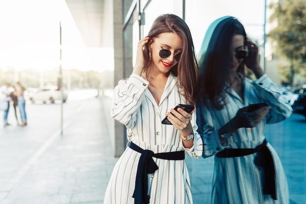 Feliz mulher jovem e atraente em óculos de sol, olhando para a tela do smartphone