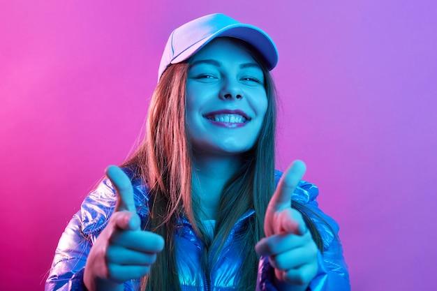 Feliz mulher jovem e bonita apontando com o dedo indicador