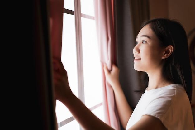 Feliz mulher jovem e bonita asiática abrindo a cortina da janela de manhã