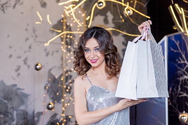 Feliz mulher jovem e bonita de vestido preto com sacolas sobre luzes
