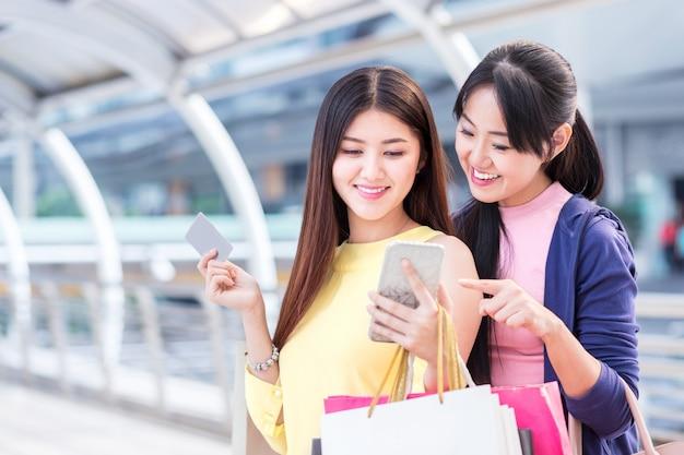 Feliz mulher jovem e bonita desfrutar de compras com sacola de compras e