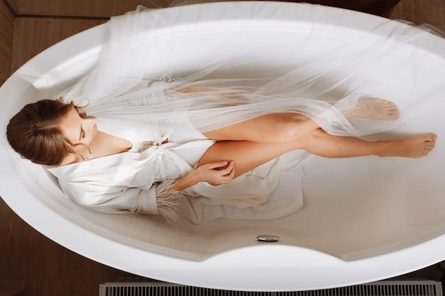 Feliz mulher jovem e bonita está usando um véu longo branco, roupão e cueca sentado na banheira em um fundo branco, relaxe.