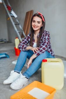 Feliz mulher jovem e bonita fazendo pintura de parede, enquanto está sentado no chão