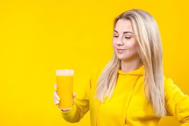 Feliz mulher jovem e bonita loira com roupas esportivas casuais amarelas, segurando o copo de suco de laranja