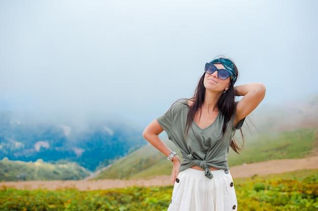 Feliz mulher jovem e bonita nas montanhas no fundo do nevoeiro