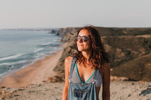 Feliz mulher jovem e bonita no topo de uma colina, apreciando o pôr do sol. horário de verão. estilo de vida