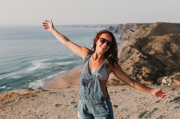 Feliz mulher jovem e bonita no topo de uma colina com os braços bem abertos. horário de verão. estilo de vida