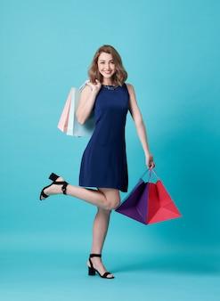 Feliz mulher jovem e bonita no vestido azul e mão segurando a sacola de compras