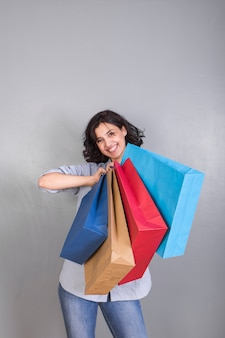 Feliz, mulher jovem, em, camisa, com, bolsas para compras