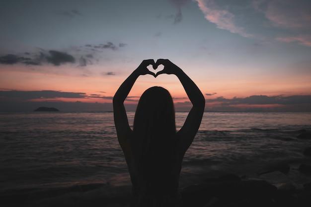 Feliz, mulher jovem, em, vestido, desfruta, dela, praia tropical, férias, em, pôr do sol