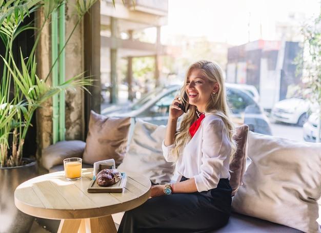 Feliz, mulher jovem, falando telefone móvel, com, pão assado, e, suco, ligado, tabela