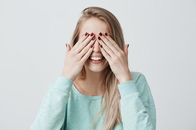 Feliz mulher jovem feliz com cabelos loiros, fecha os olhos com as mãos