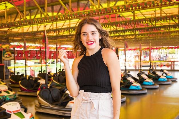 Feliz, mulher jovem, ficar, frente, choque, car, passeio, em, parque divertimento