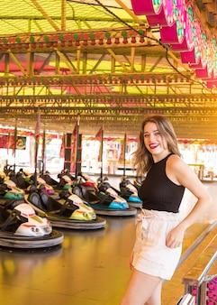 Feliz, mulher jovem, ficar, perto, a, pára-choques, passeio carro, em, parque divertimento
