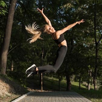 Feliz, mulher jovem, pular, parque