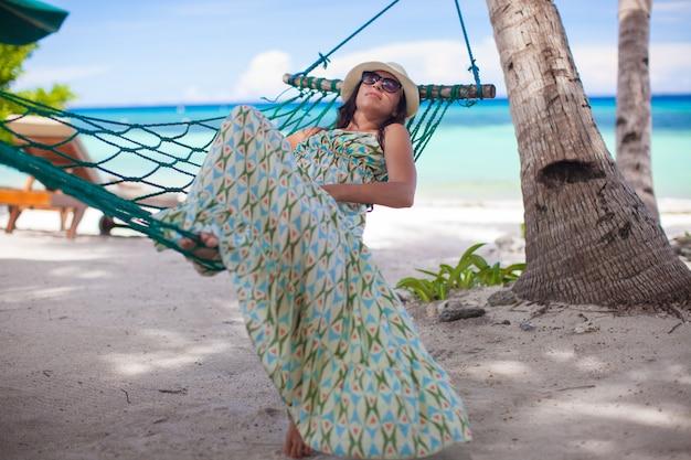 Feliz, mulher jovem, relaxante, em, a, rede, ligado, dia ensolarado