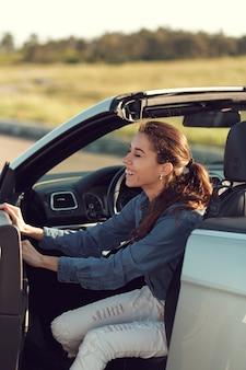 Feliz mulher jovem sentada no carro dela