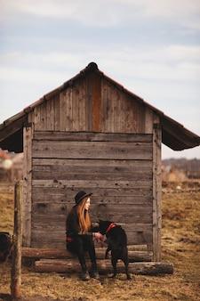 Feliz, mulher jovem, sentando, com, dela, cachorro preto