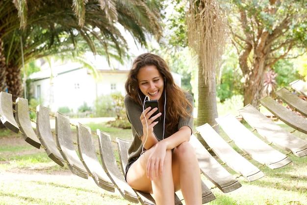 Feliz, mulher jovem, sentando, em, rede, escutar música