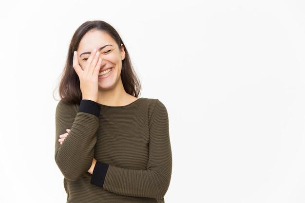 Feliz mulher latina alegre tocando o rosto e rindo