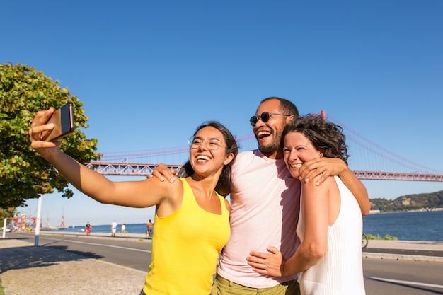 Feliz mulher latina tomando selfie de grupo