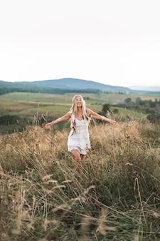 Feliz mulher loira atraente boho em vestido branco e acessórios de penas no cabelo no campo de verão ao ar livre