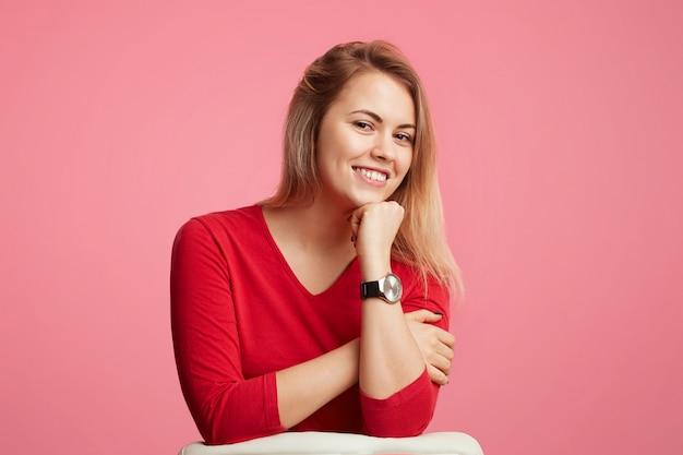 Feliz mulher loira atraente confiante mantém a mão sob o queixo, tem um sorriso brilhante, veste blusa vermelha, isolada sobre parede rosa. muito linda fêmea posa sozinha no estúdio, estar de bom humor