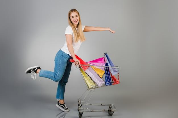 Feliz mulher loira bonita tem carrinho de compras com sacolas coloridas isoladas sobre cinza