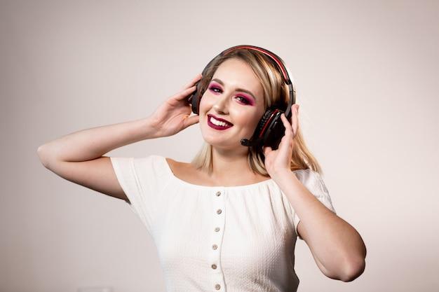 Feliz mulher loira com maquiagem brilhante e fones de ouvido gosta de música
