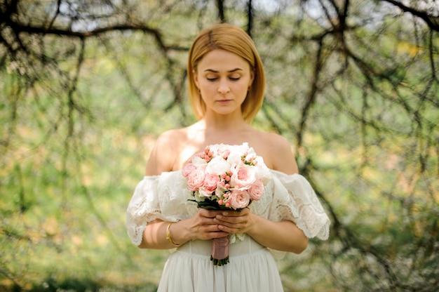 Feliz mulher loira de vestido branco com um buquê no fundo da árvore