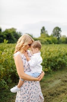 Feliz mulher loira e menino bonitinho em pé no jardim de verão