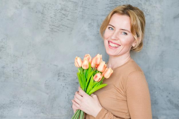 Feliz mulher loira em pé com buquê de tulipas