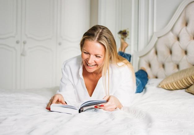 Feliz mulher loira encantadora, com longos cabelos louros em roupas casuais, lendo o livro na cama no interior rico brilhante