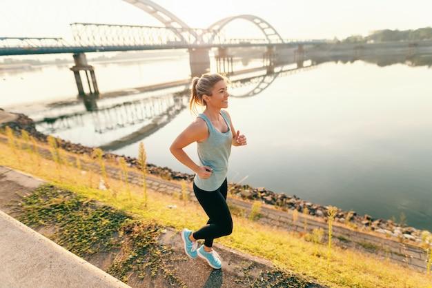 Feliz mulher loira esportiva no sportswear correndo pelo rio pela manhã.