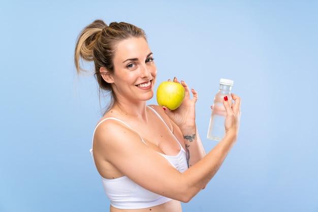 Feliz mulher loira jovem com uma maçã e uma garrafa de água