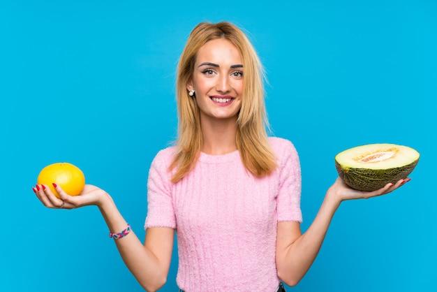 Feliz mulher loira jovem segurando frutas