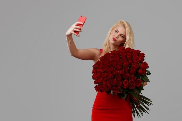 Feliz mulher loira jovem segurando um grande buquê de rosas vermelhas como um presente para 8 de março ou dia dos namorados. ela tira uma selfie em um telefone móvel