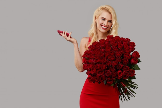 Feliz mulher loira jovem segurando um grande buquê de rosas vermelhas como um presente para 8 de março ou dia dos namorados.