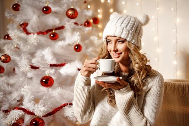 Feliz mulher loira tomando café, sala interior com decoração de natal