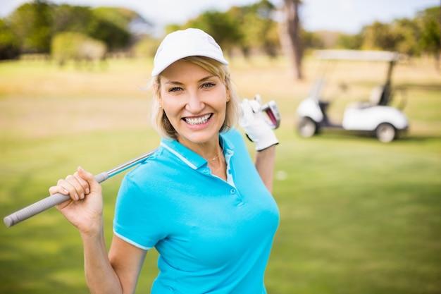 Feliz mulher madura carregando taco de golfe