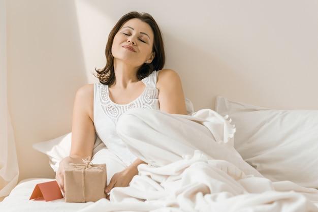 Feliz mulher madura em casa na cama, desfrutando de um presente surpresa