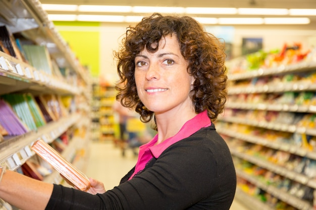 Feliz mulher madura, fazer compras na mercearia