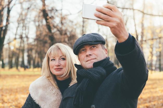 Feliz mulher madura loira e bela morena de meia-idade tirar selfie no celular