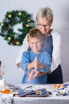 Feliz mulher madura sênior, avó e menino, neto cozinhando, amassando massa, assando torta, bolo, biscoitos. tempo para a família na cozinha aconchegante. atividade de natal sazonal de inverno em casa.