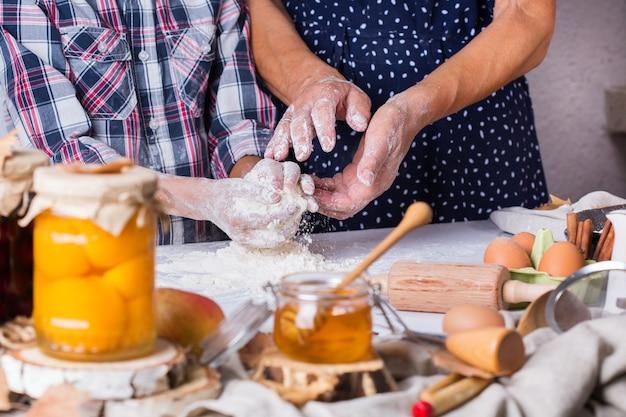 Feliz mulher madura sênior, avó e menino, neto cozinhando, amassando massa, assando torta, bolo, biscoitos. tempo para a família na cozinha aconchegante. atividade de outono em casa.