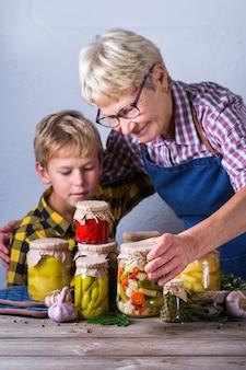 Feliz mulher madura sênior, avó e menino, neto segurando nas mãos potes com comida caseira conservada e fermentada, legumes em conserva e marinados. preservação da colheita, tempo para a família
