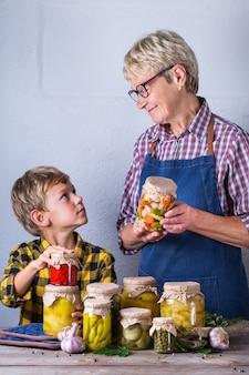 Feliz mulher madura sênior, avó e menino, neto segurando nas mãos potes com comida caseira em conserva e fermentada, legumes em conserva e marinados. preservação da colheita, tempo para a família